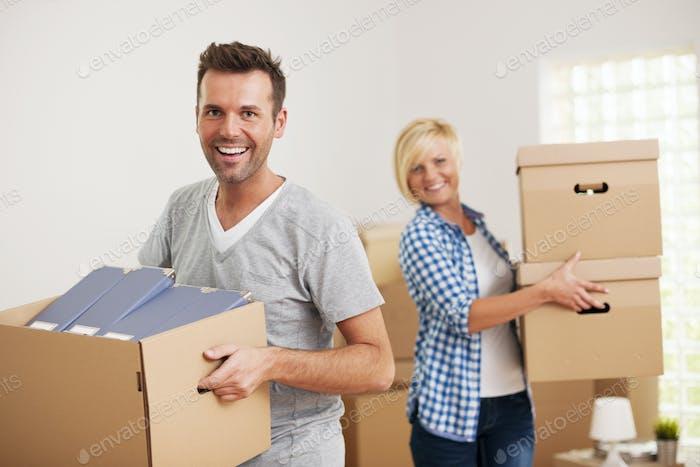 Porträt des glücklichen Paares mit Kartons in neues Zuhause