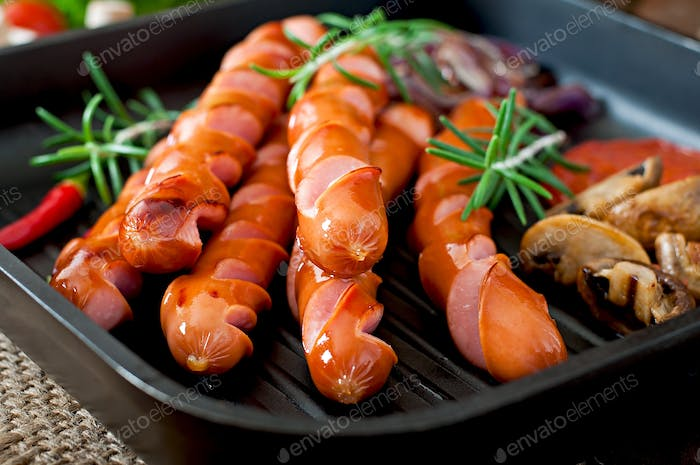Grilled sausages with vegetables on a frying pan