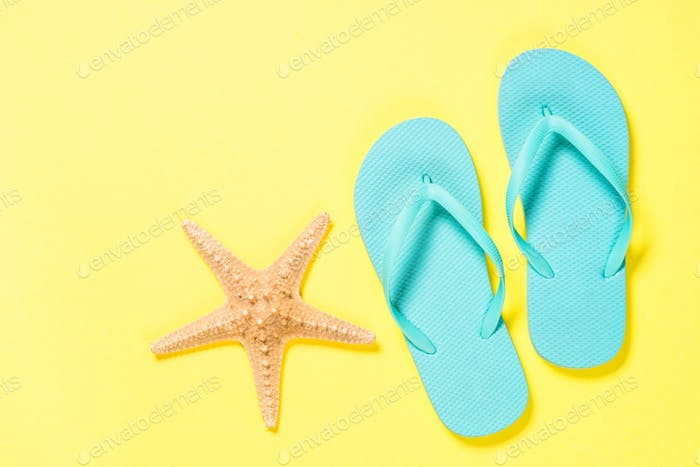Blue flip flops and starfish on yellow background