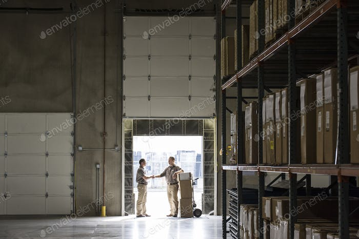 Two warehouseworkers shaking hands in the door of a loading dock in a warehouse.