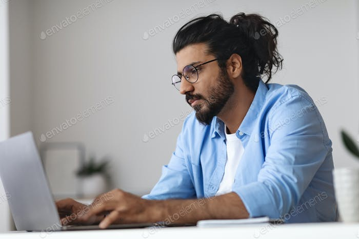 Young Western Employee Working On Laptop At Desk In Office