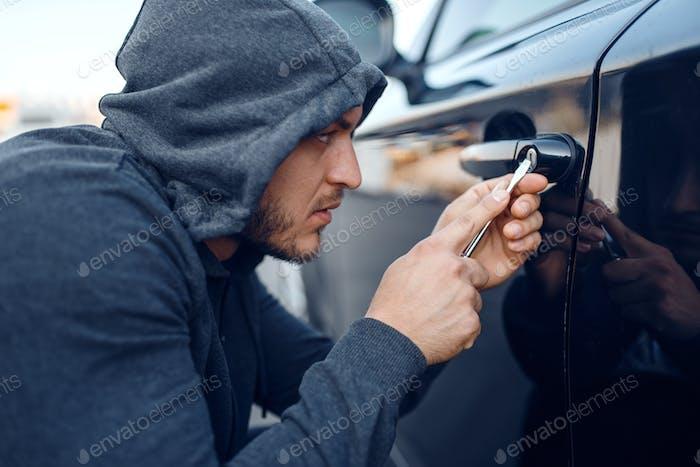 Car thief with screwdriver breaking door lock