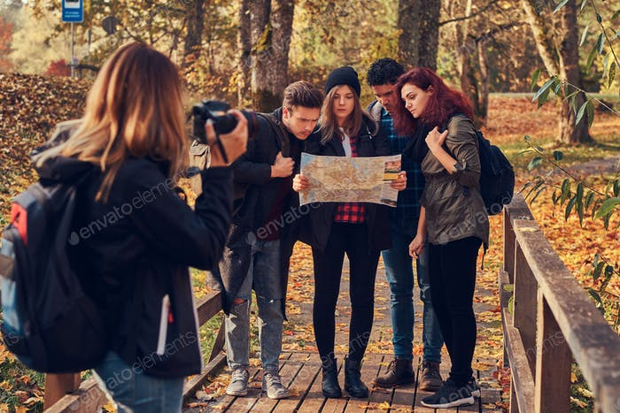 Girl taking a photo of her friends. Group of young friends hiking through forest.