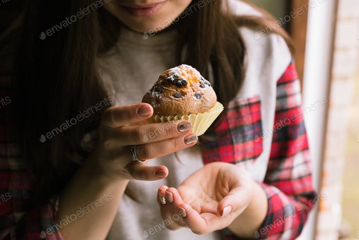 Muffin on girl hands. Close up.