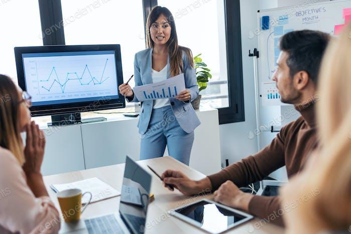 Elegante mujer de negocios inteligente explicando un proyecto a sus colegas en el ordenador en el lugar de coworking.