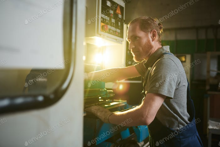 Worker working on lathe
