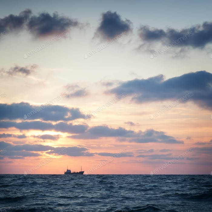 Ship in the sea against the sky with clouds at sunset