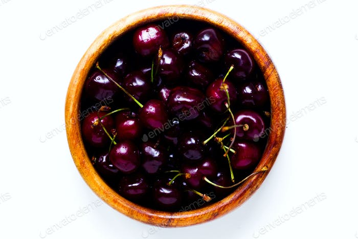 Cherry berries in a wooden plate on a white background