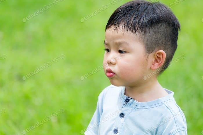 Маленький мальчик смотрит на другую сторону с забавным лицом