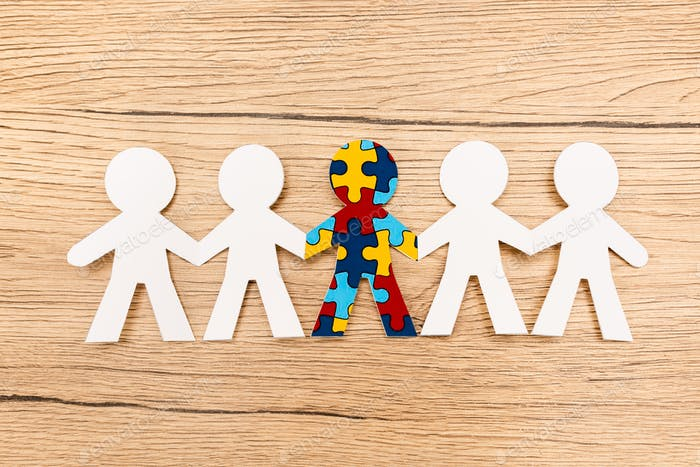 Top view of special kid with autism among another on wooden background