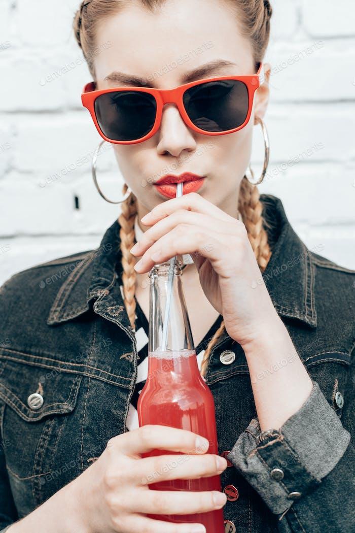 Junge Frau trinken bunten Cocktails aus Flaschen