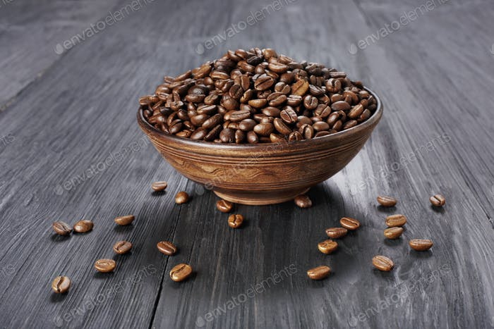 Coffee beans in bowl at wood background