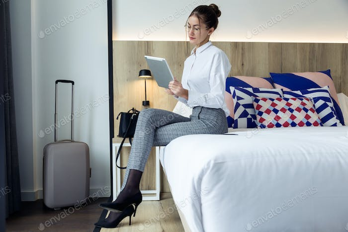 Attractive young businesswoman using her digital tablet sitting