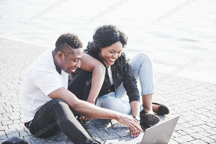 Two happy friends of students or business partners are sitting outdoors and enjoying a laptop
