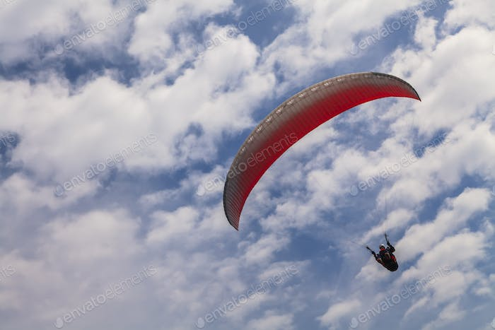 Flying paraglider on a background of blue sky and white clouds