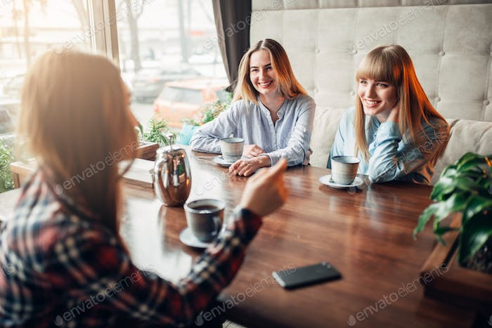 Happy girlfriends drinks coffee at the table