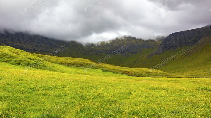 Green grass and mountains a cloudy day at Faroe Islands