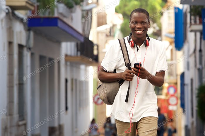 african guy walking on street with a phone