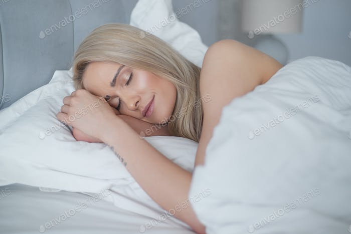 Young beautiful blonde woman sleeping in her bedroom