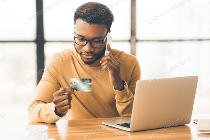 African man talking on phone holding credit card