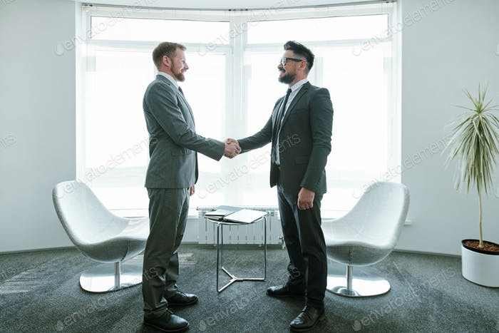 Two young successful businessmen in suits shaking hands after negotiation