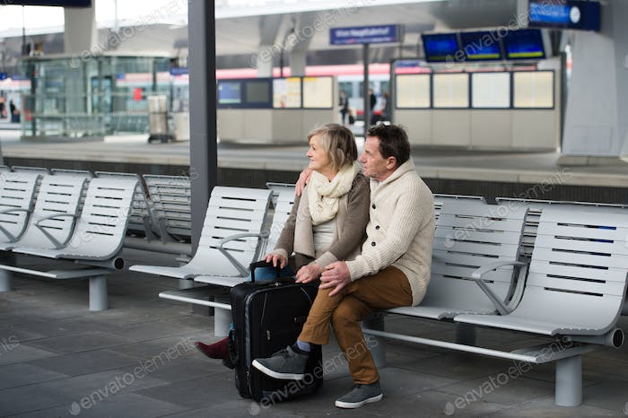 Senior couple waiting on train station, looking at watch.