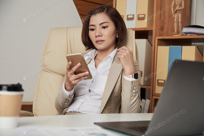 Formal businesswoman using phone in office