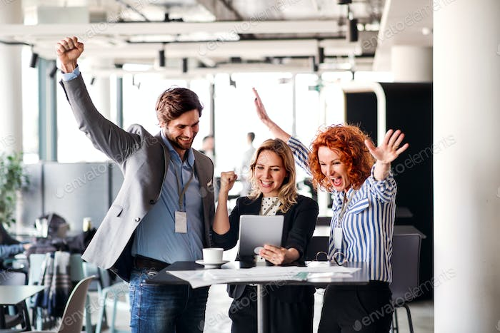 A group of business people standing in an office, expressing excitement