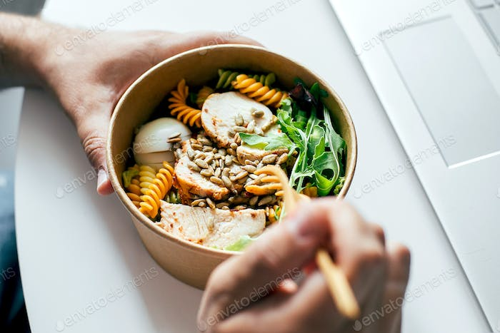 Eating healthy lunch bowl in man' s hands. Home office, food delivery, detox, food concept