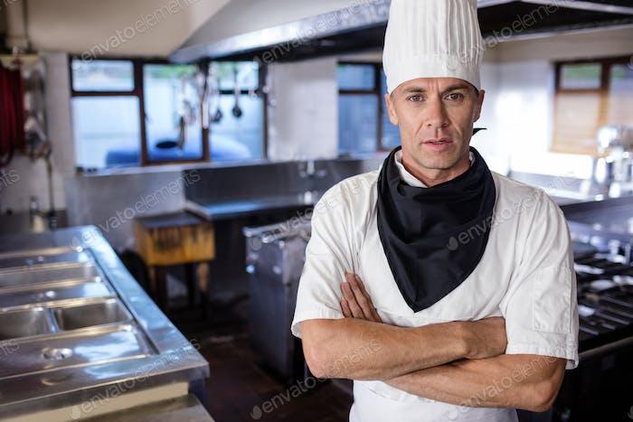 Chef masculino de pie con los brazos cruzados en la cocina