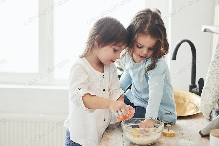 Preschool friends learning how to cook with flour in the white kitchen