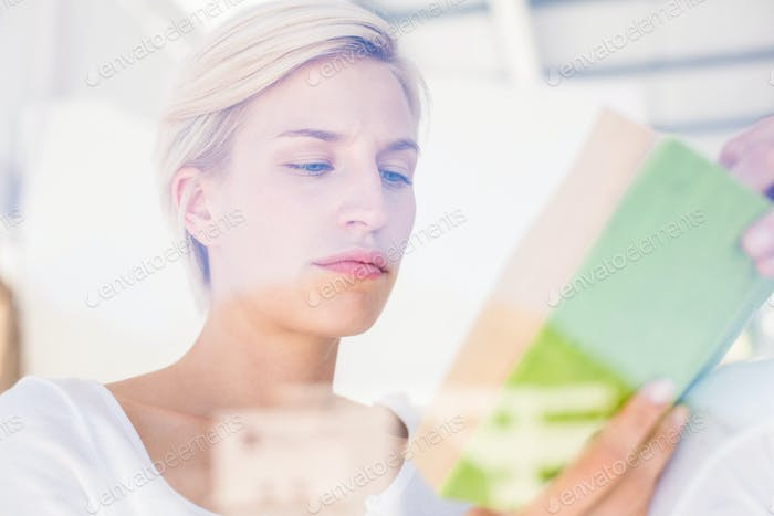 Thoughtful blonde woman reading a book in the bedroom