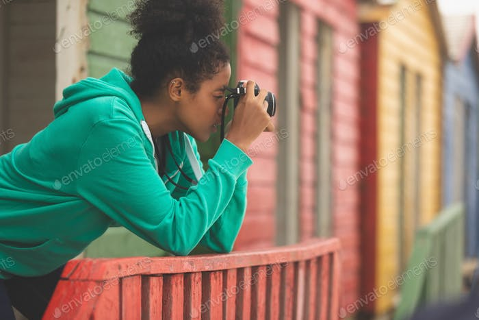 Side view of beautiful Mixed-race woman capturing photograph while standing at beach hut