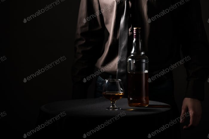 Bottle with an alcoholic drink and a glass