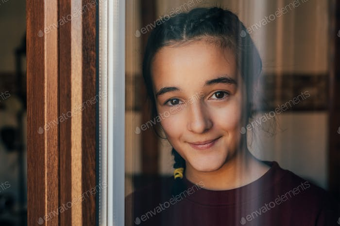 Portrait of a young teenager girl standing looking throughout the window