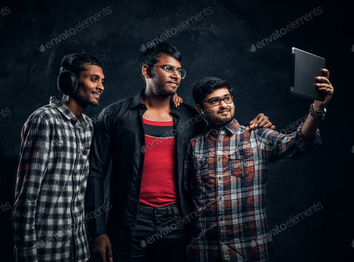 Drei glückliche indische Freunde in lässiger Kleidung stehen in einer Umarmung und nehmen Selfie auf seinem Tablet.