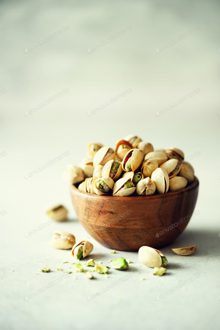 Green salted pistachios in wooden bowls on light concrete background. Copy space for your text