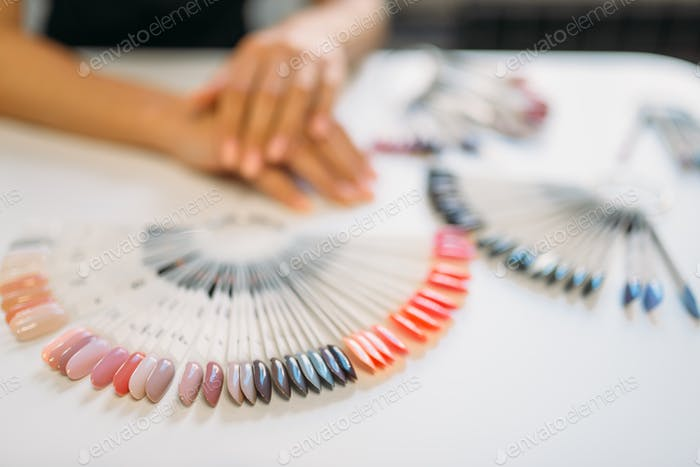 Well-groomed female hands against nail sample fan