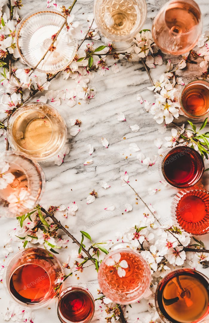 Shades of rose wine over white marble background, copy space