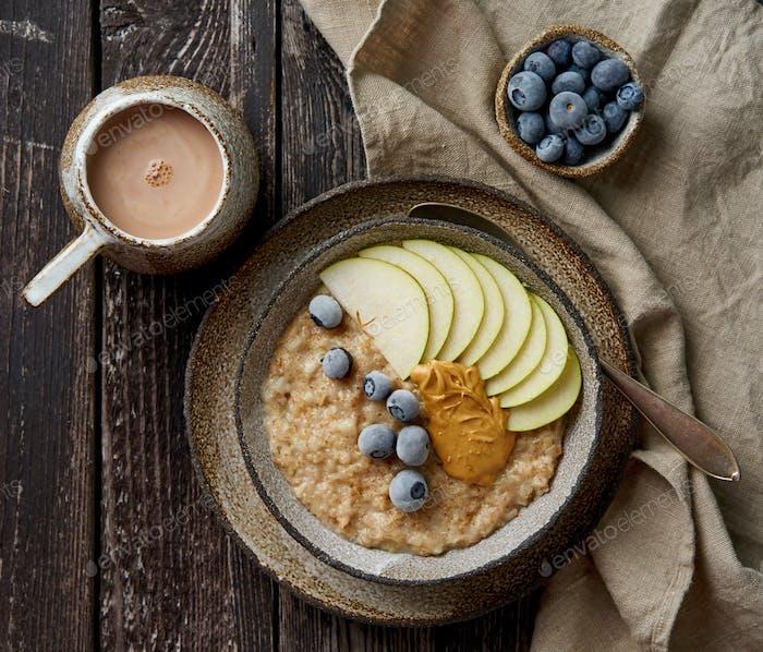 Haferflocken, gesunder Brei in großer Schüssel mit Früchten und Beeren zum Frühstück, Tasse Kakao.