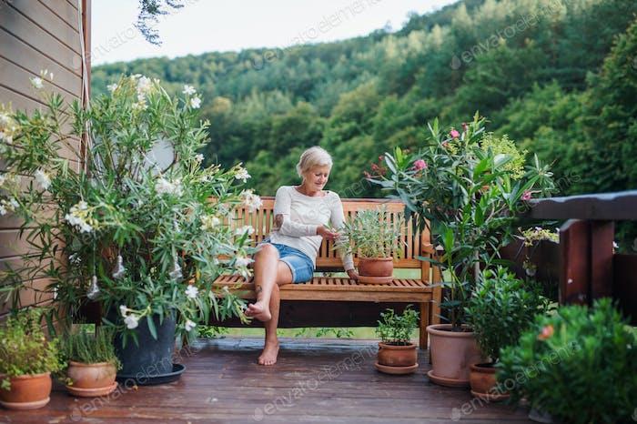 Eine Seniorin sitzt im Freien auf einer Terrasse im Sommer und ruht aus.