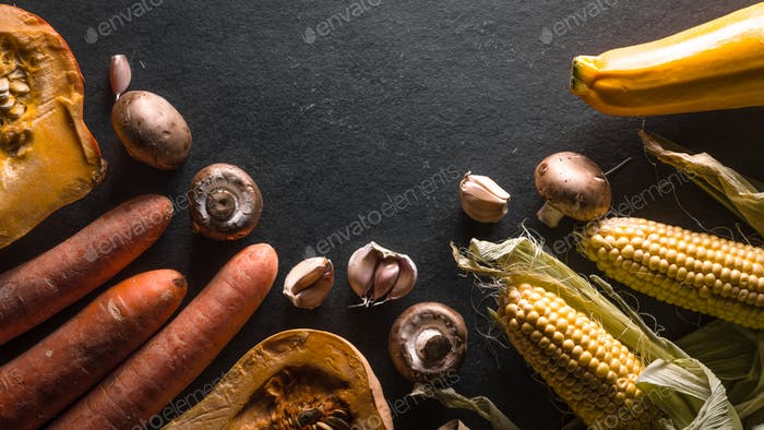 Half-frame of vegetables and mushrooms on a gray stone