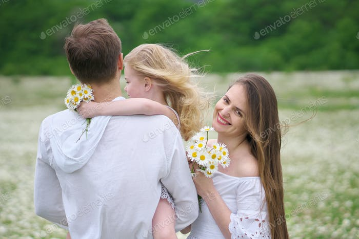 Happy family on camomile meadow.