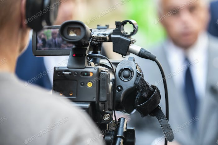 Press Conference Outdoors. Cameraman at a Media Event