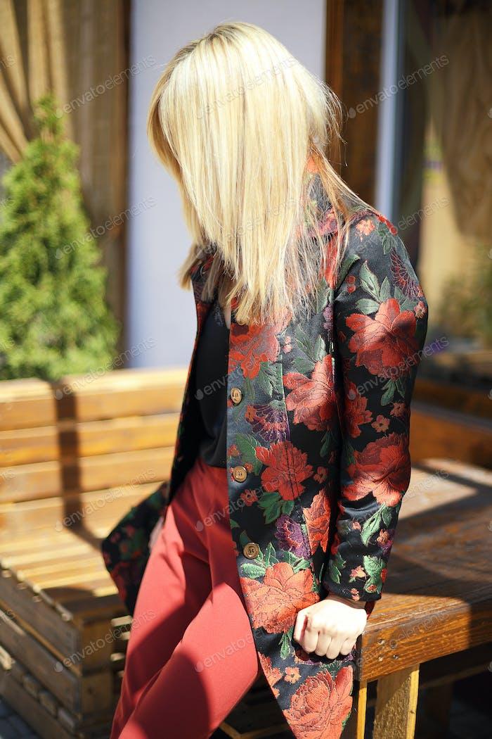 junge schöne stilvolle Frau posiert auf der Straße in Blumendruck