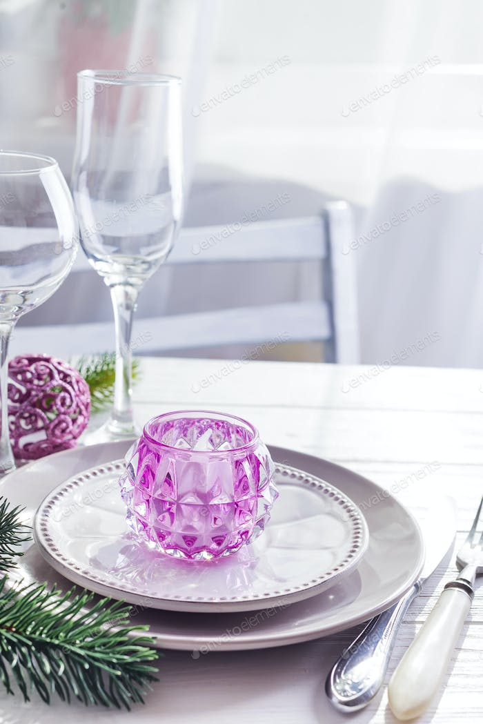 Place table setting for Christmas white table with purple decor elements with green branches