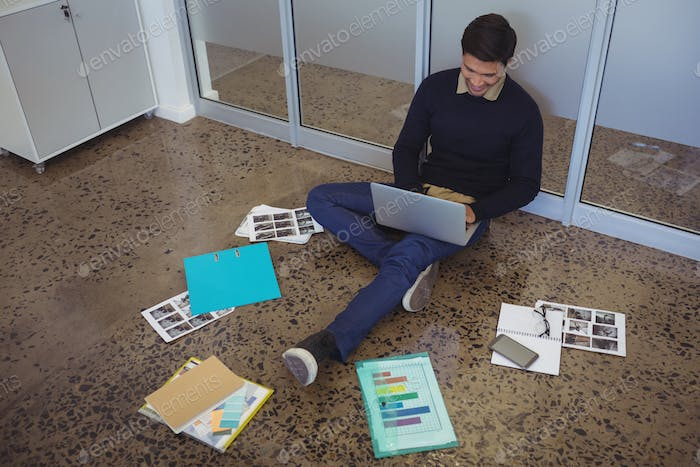 Young businessman sitting on floor while working in creative office
