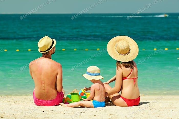 Familie am Strand. Kleinkind spielt mit Mutter und Vater.