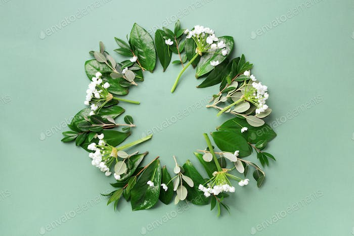 Creative layout made of tropical leaves and white flowers on green background. Top view. Flat lay