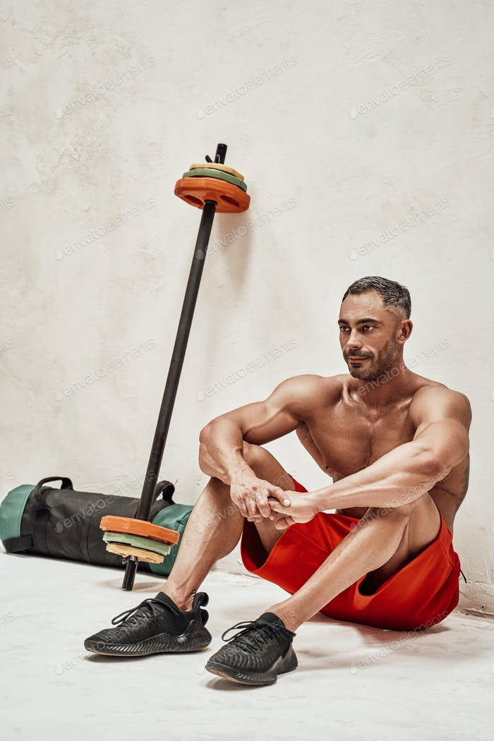 Embossed fitness couch posing in a studio with fitness gear looking ready to workout